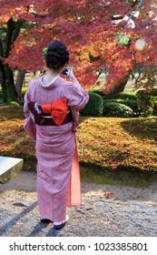 Kanazawa, Japan. 11 17 2017. Girl in traditional Kimono in kanazawa garden in autumn.