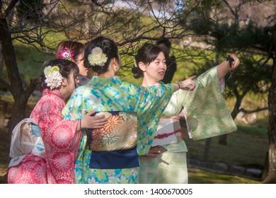 Kanazawa Japan Mar 13th 2018: Japanese ladies wearing Kimono are doing selfie in Kenroku-en.   Kenroku-en is an old private garden and one of the Three Great Gardens of Japan.