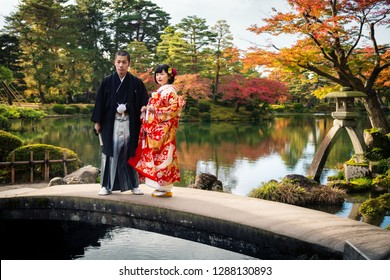 KANAZAWA, JAPAN - NOVEMBER 15, 2018: Wedding couple in traditional kimono posing for pre-wedding photosession on a bridge in Kenrokuen garden during momiji season, Kanazawa city, Ishikawa, Japan.