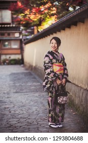 KANAZAWA, JAPAN - NOVEMBER 28: Japanese girl in kimono posing in Nagamachi samurai district. The area preserves samurai residences, earthen walls, entrance gates, narrow lanes and water canals.