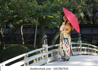 KANAZAWA, JAPAN - October 14, 2013: A beautiful young Japanese woman in traditional kimono stands on a bridge with a sun umbrella in Kenrokuen park, Kanazawa City, Ishikawa, Japan