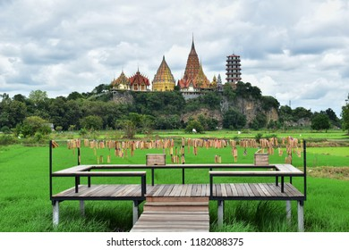 Kanchanaburi, Thailand​ -​ September​ 14, 2018​: View​ of green​ field​ and Tiger​ cave​ temple (Wat Tham Sua)​ from Meena​ cafe, Kanchanaburi, Thailand.