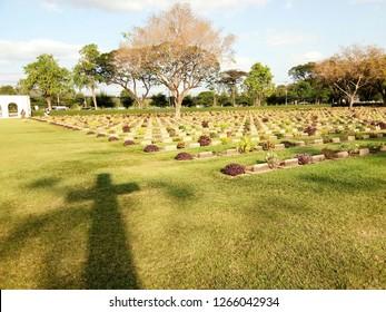 Kanchanaburi city/ Thailand - July 2017: Shadow of the cross on the lawn yard in Kanchanaburi World War II Cemetery where located in Kanchanaburi province, Thailand
