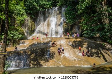 Kanchanaburi, Thailand -  October 7, 2018: Tourists playing Sai Yok Noi Waterfall to cool off in holiday