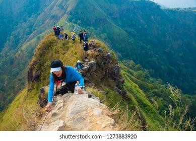 Kanchanaburi, Thailand - 28 December 2018: Female tourists are climbing a rock at Khao Chang Phueak National Park, Thong Pha Phum, Kanchanaburi, Thailand