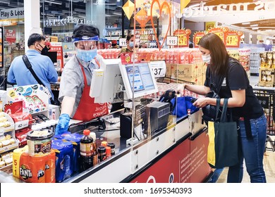KANCHANABURI, THAILAND - APRIL 6,2020: Unidentified Cashier or supermarket staff and customers in medical protective mask  To prevent the spread of germs (Covid-19) at Top Supermarket on april 6,2020