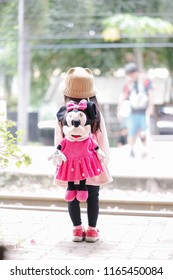 Kanchanaburi, Thailand - August 26, 2018 : A photo of unidentified little girl in pink coat wearing a cute Minnie Mouse backpack waiting at a train station. Processed in high key photography.