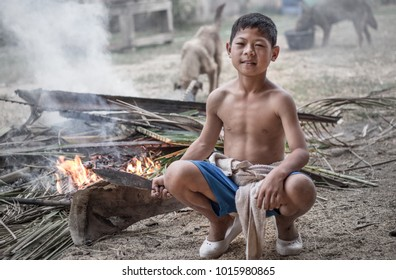 Kanchanaburi, Thailand - CIRCA January 2014: a native minority boy using traditional knife to chop wooden materials for firewood, he live near border of Thailand and Myanmar in country side.