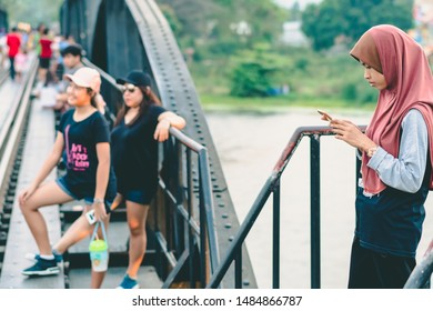 KANCHANABURI THAILAND - FEBRUARY 9 : Unidentified Muslim woman relax and admire the beautiful scenery in the evening at The Bridge of the River Kwai on February 9,2019  in Kanchanaburi, Thailand