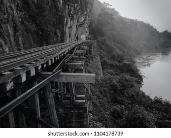 Kanchanaburi, Thailand- January 13, 2018: The peaceful atmosphere of  the World War II Death Railway in the early morning with few people walking on the train track.