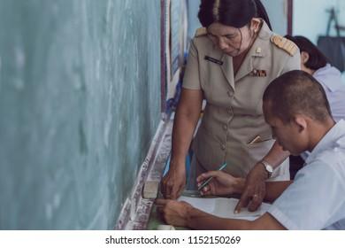 KANCHANABURI THAILAND - JULY 16 :  Unidentified Good teacher give midterm exam questions to students in the classroom on July 16,2018 at Watkrangthongratburana school in Kanchanaburi, Thailand