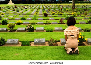 Kanchanaburi, Thailand - July 2, 2016: Asian woman sitting in front of black gravestone at graveyard. Reminisce, miss, sad and lose person in the family or important people concept