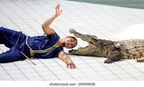 KANCHANABURI, THAILAND - June 13: Trainer puts his head in a crocodile mouth at show in Safari Park on June 13, 2015. This popular and exciting show is very famous among tourist and Thai people.
