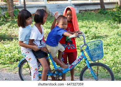 Kanchanaburi, Thailand - June 2, 2013: Children having fun riding with favorite bicycles.