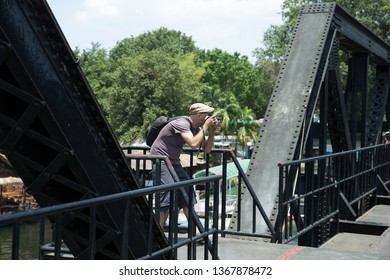 Kanchanaburi, THAILAND - March 29, 2019: Tourist taking a Photo with friend on the death railway bridge.