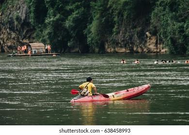 KANCHANABURI, THAILAND - MAY 6, 2017: People kayak on river  near the wooden home raft floating at river kwai at sai yok,kanchanaburi,thailand