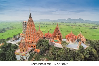 Kanchanaburi -THAILAND, Oct. 15, 2016 : Top view of Wat Tham Khao Noi and Wat Tham Sua, chinese shrine temple on top hill with green rice fields and blue sky background.