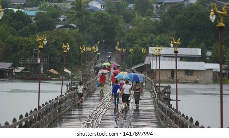 KANCHANABURI, THAILAND – OCTOBER 05, 2012: People walk on old wooden bridges while the rain is falling. It is the way of life of the Mon community in Sangkhla Buri District, Kanchanaburi Province.