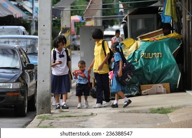 KANCHANABURI, THAILAND - SEPTEMBER 3: Local school children in uniform walking along the footpath in the town of Kanchanaburi, Thailand on the 3 September, 2014.