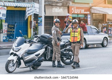 KANCHANABURI, THAILAND-APRIL 17,2019: Unidentified two employees of the traffic road police in uniforms with police motorcycles serve on the city street on the road with transport on Songkran festival