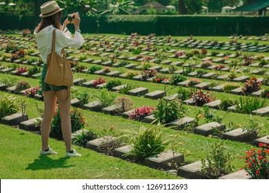 KANCHANABURI,THAILAND-DECEMBER 19 : Unidentified tourists walk and take photography at Kanchanaburi Allied War Cemetery on December 19,2017 in Kanchanaburi, Thailand.
