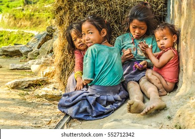 Kanchenjunga Trek, Nepal - circa April 2012: Four young girls with bare feet sit on ground and play in Kanchenjunga Trek, Nepal. Documentary editorial.