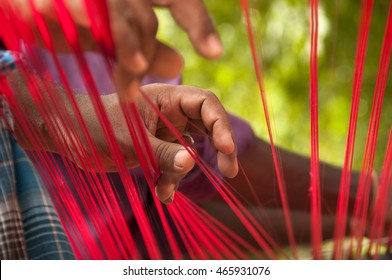 KANCHIPURAM, INDIA - 18 AUGUST 2010 : unidentified  weavers Removing knots and drying silk yarn for  weaving silk sari on loom. Kanchipuram is famous for hand woven silk sarees.