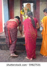 KANCHIPURAM, INDIA - NOV 27 : Hindu women make puja offering at small Hindu shrine within the temple  on Nov 27, 2009 near Kanchipuram, India