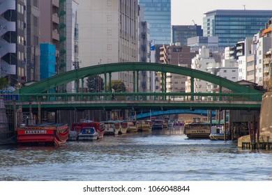 KANDA RIVER, TOKYO, JAPAN - MARCH 3RD, 2018. Traditional 'Yakatabune' pleasure boats tied up in the Kanda River, near the famous historic Yanagi Bashi Bridge in central Tokyo.