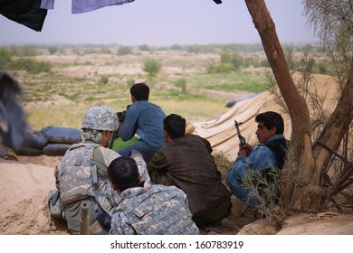 KANDAHAR, AFGHANISTAN - AUGUST 2010: US Army Soldiers and Afghan Police attempt to identify the location from which Insurgents are firing.