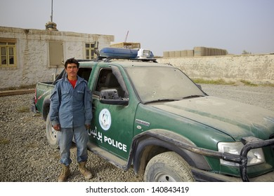 KANDAHAR, AFGHANISTAN - AUGUST 27: An Afghan policeman stands next to his truck that had just been hit by an improvised explosive device on August 27, 2010 in Kandahar Province Afghanistan.