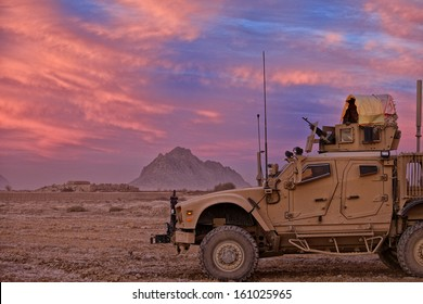 KANDAHAR, AFGHANISTAN - DECEMBER 2010: Soldiers watch from their All Terrain MRAP as the sun sets over Kandahar Province, Afghanistan.