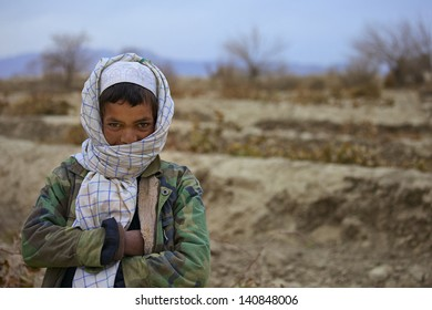 KANDAHAR, AFGHANISTAN - JANUARY 10: An Afghan boy sports a camo patterned jacket to stay warm while gathering firewood on January 10, 2011 in Kandahar Province Afghanistan.