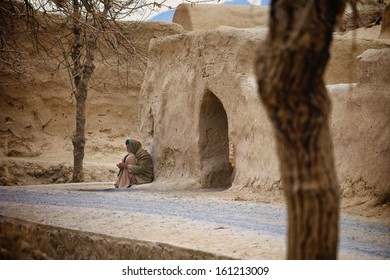 KANDAHAR, AFGHANISTAN - JANUARY 2011: An Afghan village elder sits outside on the road, waiting for call to the evening call to prayer in Kandahar Province, Afghanistan.