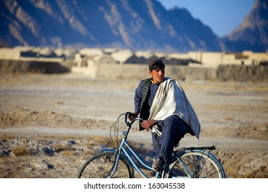 KANDAHAR, AFGHANISTAN - JANUARY 22, 2011: A young Afghan Man pauses his bike ride to observe an ISAF patrol heading down the street in Kandahar Province, Afghanistan.