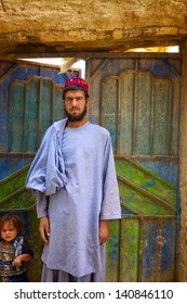 KANDAHAR, AFGHANISTAN - JUNE 1: A young Afghan man poses in front of his home as a patrol walks by on June 1, 2010 in Kandahar Province Afghanistan.