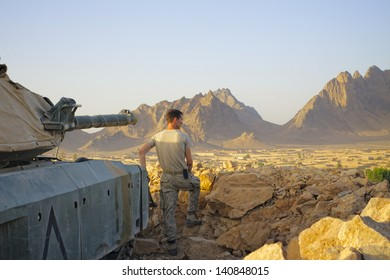 KANDAHAR, AFGHANISTAN - JUNE 20: An ISAF Soldier looks out over the village below his position as the sun sets on June 20, 2010 in Kandahar Province Afghanistan.