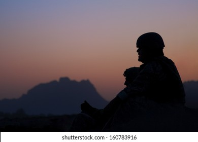 KANDAHAR, AFGHANISTAN - JUNE 2010: A soldier and interpreter watch the blast of an IED being safely destroyed as dusk turns into night in Kandahar, Afghanistan.