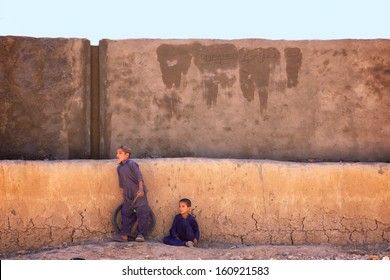 KANDAHAR, AFGHANISTAN - JUNE 2010: Two Afghan children rest in the shade of a newly built town hall building on a hot summer day in Kandahar Province, Afghanistan.