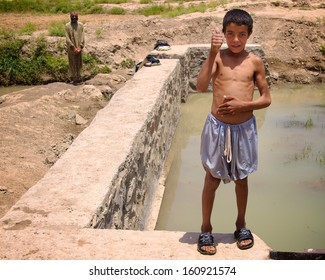 KANDAHAR, AFGHANISTAN - JUNE 2010:  A young Afghan takes a break while helping his father build a retaining wall on an irrigation ditch in Kandahar Province, Afghanistan.