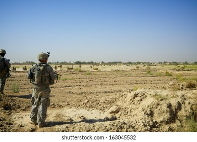 KANDAHAR, AFGHANISTAN - JUNE 22, 2010: An American Soldier watches as a long column of Afghan Soldiers move into a Village on a mission in Kandahar Province, Afghanistan.