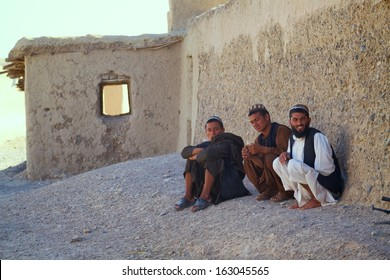 KANDAHAR, AFGHANISTAN - MAY 14, 2010: Three Afghan Men sit alongside a street and watch an ISAF patrol in Kandahar Province, Afghanistan.