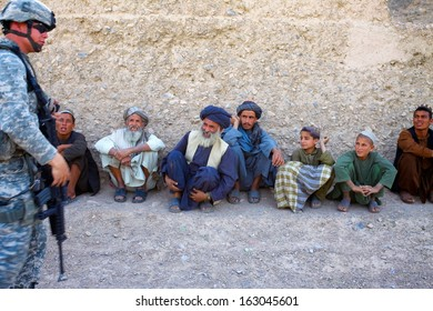 KANDAHAR, AFGHANISTAN - MAY 14, 2010: Afghan sit along a wall and laugh at the interpreters jokes as ISAF Forces speak with the village leaders in Kandahar Province, Afghanistan.