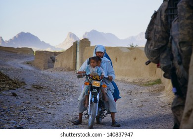 KANDAHAR, AFGHANISTAN - MAY 14: An entire Afghan Family rides home on one motorcycle on May 14, 2010 in Kandahar Province Afghanistan.