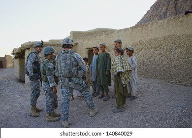 KANDAHAR, AFGHANISTAN - MAY 14: ISAF Forces talk to children on the side of the road on May 14, 2010 in Kandahar Province Afghanistan.