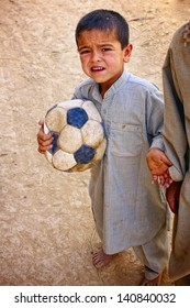 KANDAHAR, AFGHANISTAN - MAY 22: A young Afghan boy looks like he needs a new soccer ball on May 22, 2010 in Kandahar Province Afghanistan.