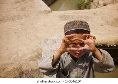KANDAHAR, AFGHANISTAN - MAY 22: A young Afghan boy mimics taking a picture on May 22, 2010 in Kandahar Province Afghanistan.