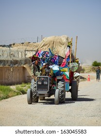 KANDAHAR, AFGHANISTAN - MAY 25, 2010: A typical Afghan Tractor pulling an over sized load down a street in Kandahar Province, Afghanistan.