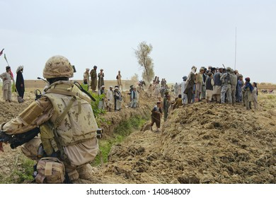 KANDAHAR, AFGHANISTAN - MAY 8: ISAF forces observe the progress as Afghan villagers dig a new irrigation canal for their farms on May 8, 2010 in Kandahar Province Afghanistan.