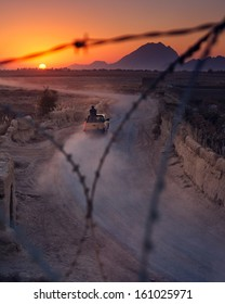 KANDAHAR, AFGHANISTAN - NOVEMBER 2010: Afghan police ride off into the sunset to respond to an explosion down to road in Kandahar, Afghanistan.